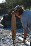 Man with hat splits cedar for firewood at a campsite on beach on west coast of Vancouver Isaland royalty free stock images