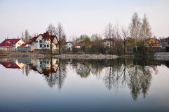 Spring landscape. Of private buildings in a suburb, reflection in a lake Stock Photos
