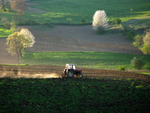 Spring landscape. With tractor and pieces of cultivated farmland and trees Stock Image