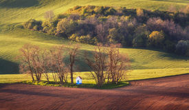 Spring landscape with amazing chapel in green fields at sunset Stock Images