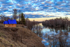 Spring landscape, bath with blue roof. On the bank of the river Royalty Free Stock Photography