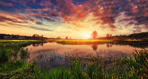 Spring landscape of bright sunrise over river with colorful cloudy sky on horizon. Scenery spring nature.  Royalty Free Stock Photos