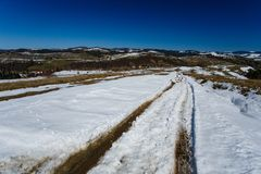 Spring landscape. Car tracks on thick snow on sunny day royalty free stock image