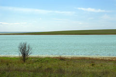 Spring landscape in cold colors. Two coastlines of a river. Spring striped geometric landscape in cold colors. Two coastlines of a river with meadow of green Stock Photography