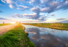 Spring landscape. Colorful blue cloudy sky reflected in water. Green grass and yellow sun, road and windmill at sunrise in Netherlands. Amazing colorful rustic Royalty Free Stock Photography