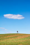 Spring landscape with field, hunting hide and blue sky Royalty Free Stock Photos