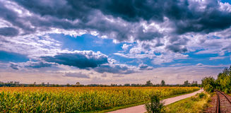 Spring landscape with field, rail road and clouds Spring background Stock Photo