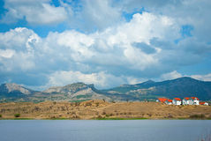 Spring landscape with houses, mountains and clouds in sky Royalty Free Stock Photo