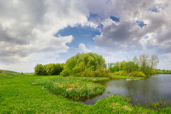 Spring landscape with lake, meadow, forest and sky with clouds Stock Image