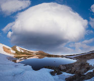 Spring landscape with a mountain lake and a cloud Royalty Free Stock Photography