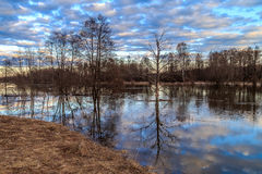 Spring landscape, pour a river flood. Ed trees and chapel Stock Photo