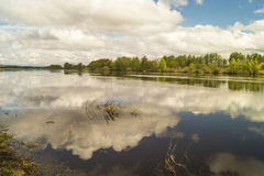 Spring landscape with river. On background beautiful sky and reflections in water Royalty Free Stock Photos