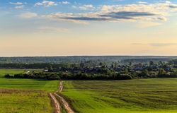 Spring landscape, the road through the field to the village. Green shoots, evening sun Stock Photos