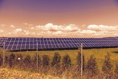 Spring landscape at sunset with solar panels. Green field Royalty Free Stock Images