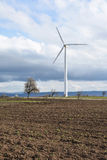 Spring landscape with wind turbine against a cloudy sky Stock Photo