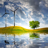 Spring landscape with wind turbine. In the sunset Stock Image