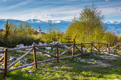 Spring landscape with wooden fence, trees, part and snowy mountains Royalty Free Stock Images