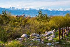Spring landscape with wooden fence, trees, part and snowy mountains Stock Photo