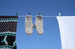 Spring laundry. Mittens, sweater and t-shirt hanging to dry on a clothes-line stock image