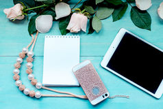 Spring layout on a blue wooden background with flowers and petals Notepad sheets for records of tablet phone and beads accessories Royalty Free Stock Photography