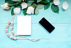 Spring layout on a blue wooden background with flowers and rose petals Notepad sheets for notes and phone and beads accessories Royalty Free Stock Photos