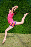Spring Leap. A young tween makes a dance leap in the grass on a spring day Royalty Free Stock Photos