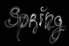 Spring lettering word written with white smoke or flame light isolated on black background stock photography