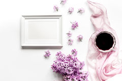 Spring lilac flowers on workdesk female home office with frame and coffee white background top view mockup. Spring lilac flowers on workdesk at female home royalty free stock photos