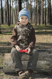 In the spring of a little boy sitting on a log in the forest. Stock Photo