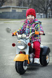 In the spring a little girl riding a motorcycle. Stock Images