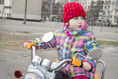 In the spring of a little girl riding a motorcycle on the street Royalty Free Stock Images