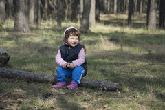 In the spring of a little girl sitting on a log in the forest. Stock Images