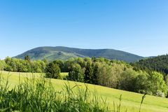 Spring meadow in mountains. Bright alpine landscape with blue sky. Bright sun in blue sky. Green fields under blue sky. Stock Image