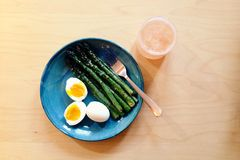 Spring meal: Asparagus and soft boiled eggs with a rhubarb drink. Grilled asparagus and soft boiled eggs are served with a fork on a blue stoneware plate. Next Royalty Free Stock Photos