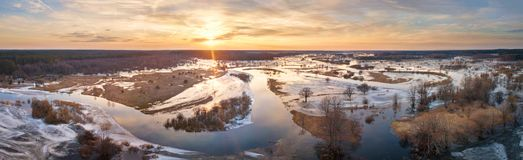 Spring melting river flood panorama. Sunset over thaw meadows. Streaming water at early springtime. Drone view Stock Photo