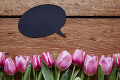 Spring message speech bubble and fresh tulips on wood. En table flowers talking ideas of communication creative ideas royalty free stock images