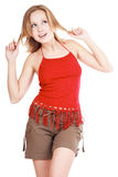 Spring mood. Pretty blond girl in red top and shorts dancing with dreamy smile Stock Photos