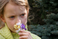 Spring mood. Young, sad girl smelling crocuses Stock Photography