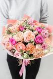 Beautiful luxury bouquet of mixed flowers in woman hand. the work of the florist at a flower shop. Vertical photo. Spring mood. beautiful luxury bouquet of mixed stock images