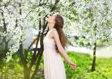Spring mood, cute girl smell flowering tree. Enjoying nature, white garden royalty free stock image