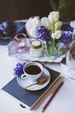 Spring morning at home with cup of coffee, book and flowers on white table. Seasonal decoration, cozy living, hygge concept stock image