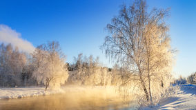 Spring morning landscape with fog and a forest on the shore of a lake, Russia, the Urals, February Royalty Free Stock Image