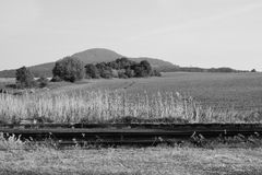 Spring morning landscape with hills, mountains and rail track in foreground near Libesice village with black and white stylization stock image