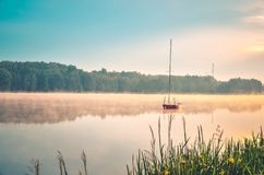 Spring morning waterfront landscape. Boat on the foggy lake royalty free stock photo