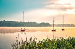 Spring morning waterfront landscape. Boats on the foggy lake stock photos
