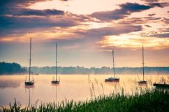 Spring morning waterfront landscape. Boats on the foggy lake stock photography