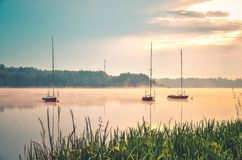 Spring morning waterfront landscape. Boats on the foggy lake stock images