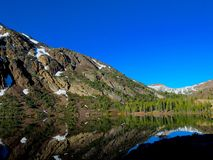 Spring Mountain with Pines Reflected in a Lake. A thawing mountain with patches of snow between pine trees is being reflected on a still lake in Yosemite Valley stock image