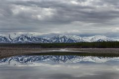 Spring mountains with remnants of snow and the reflection in the river. Royalty Free Stock Photography