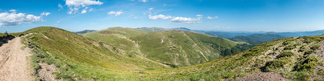 Spring mountains under blue sky with clouds - panoramic view Stock Image